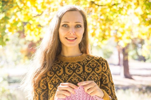 Caucasienne fille aux cheveux longs dans un pull marron souriant
