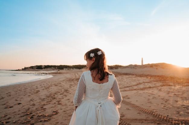 Caucasienne fille habillée en communion dans un coucher de soleil sur la plage alors qu'elle est heureuse