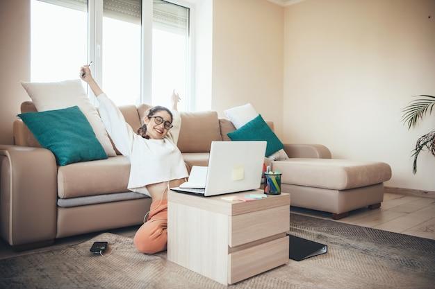 Caucasienne fille avec des lunettes ayant des leçons en ligne sur le sol à l'ordinateur portable faisant des gestes le signe oui