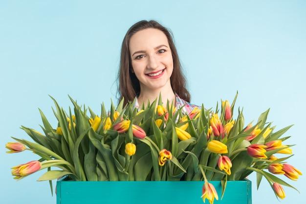 Caucasienne jeune femme avec un gros bouquet de tulipes