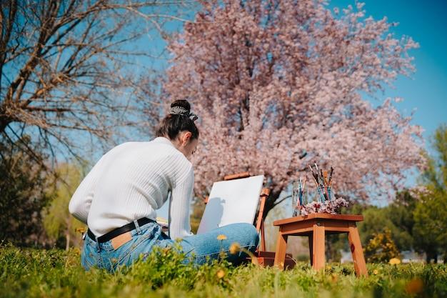 Caucasienne jeune fille aux cheveux ondulés, peindre une toile avec des peintures rose pastel en se tenant debout dans la nature d'un parc