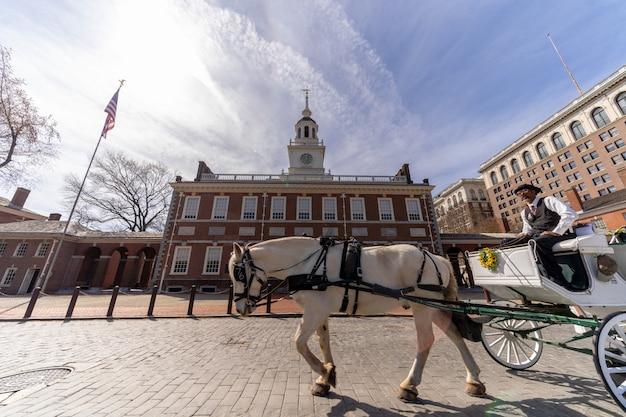 Cavalier de cheval non défini pour le touriste devant le hall de l'indépendance. crême philadelphia