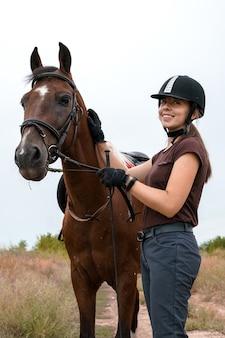 Un cavalier en gants noirs et un casque d'équitation noir se tient à côté de son pinto sellé