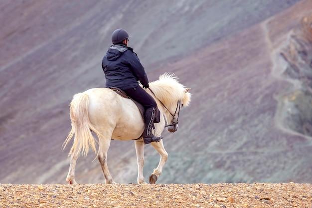 Le cavalier monte sur un cheval islandais contre un paysage de montagne