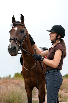 Un cavalier portant des gants noirs et un casque d'équitation noir se tient à côté de son pinto sellé, tient les rênes d'une main, caresse le cou de l'autre