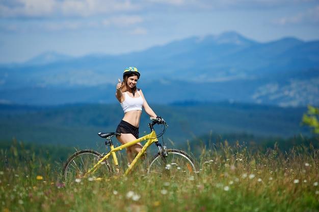 Cavalier avec vélo de montagne jaune, montrant les pouces vers le haut, debout sur l'herbe au jour d'été. montagnes, ciel bleu sur l'arrière-plan flou