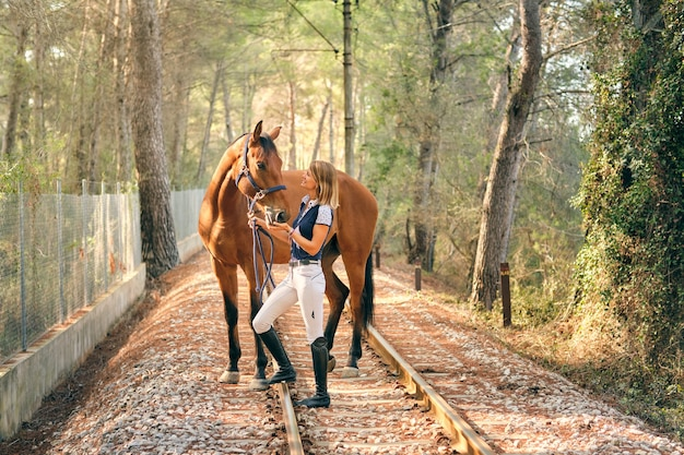 Cavalière avec cheval alezan dans les bois