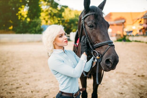 La cavalière embrasse son cheval, l'amitié, l'équitation. sport équestre, jeune femme et bel étalon, animal de ferme