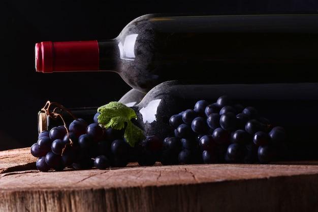 Cave à vin avec bouteille avec poussière et raisins