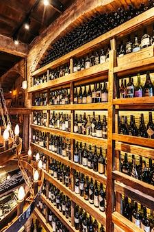 Cave à vin sur le mur dans un restaurant italien décoré de briques dans une lumière chaude qui crée une atmosphère chaleureuse.