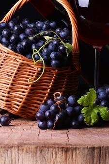 Cave à vin avec verre à vin et panier en osier avec raisins