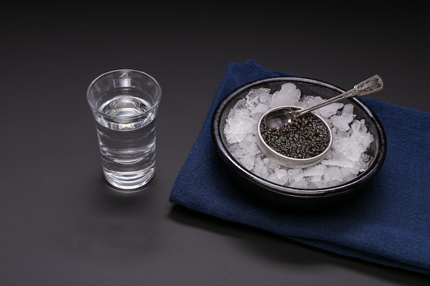 Caviar dans une boîte en métal sur fond noir