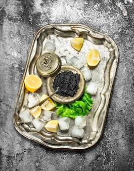 Caviar noir sur l'ancien plateau de glace. sur fond rustique.