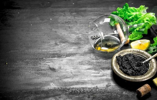 Caviar noir au vin blanc et aux herbes. sur un tableau noir.