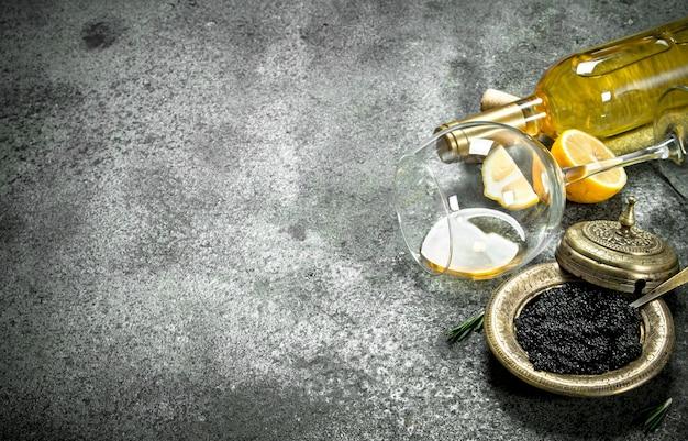 Caviar noir au vin blanc et citron. sur fond rustique.