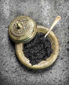 Caviar noir dans l'ancien bol. sur fond rustique.