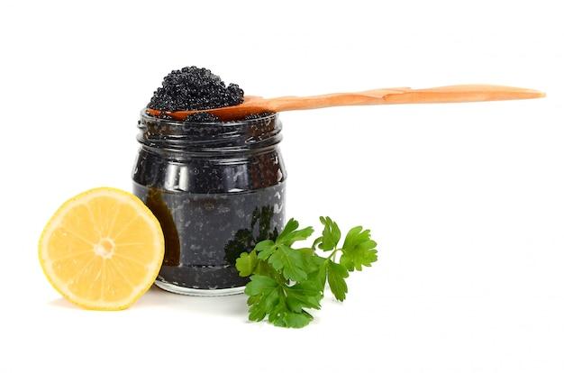 Caviar noir dans un bocal en verre avec citron et persil