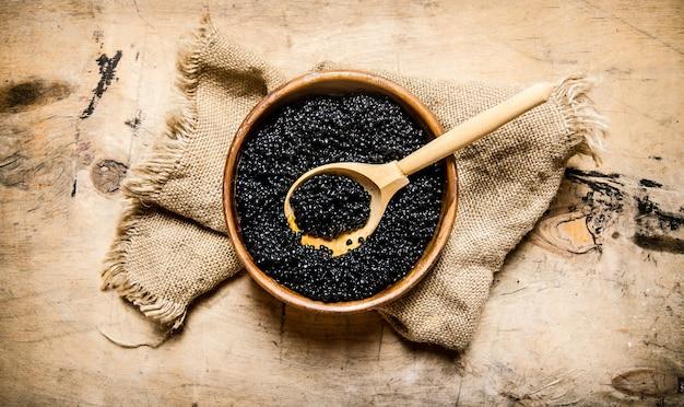 Caviar noir dans un bol en bois sur tissu ancien. sur une table en bois. vue de dessus