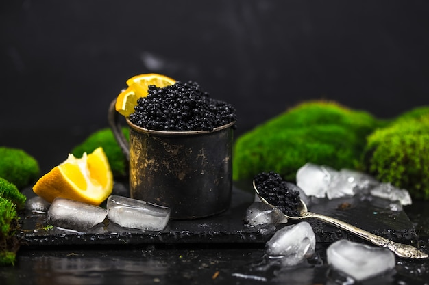 Caviar noir dans un bol. gros plan de caviar noir d'esturgeon naturel de haute qualité. épicerie fine. texture du plat carré de caviar de luxe cher sur fond noir