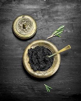 Caviar noir dans un bol. sur un tableau noir.