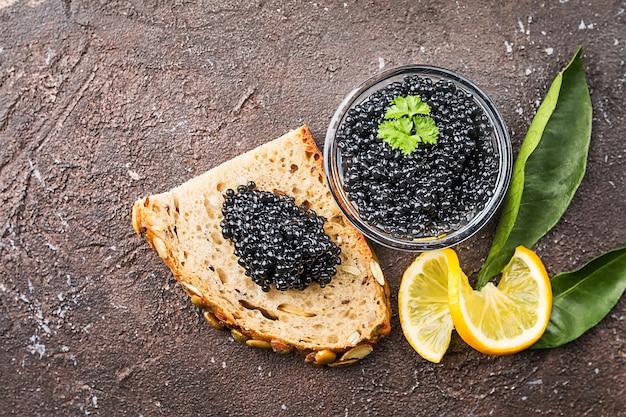 Caviar noir dans un bol en verre avec du citron close up