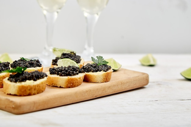 Caviar noir d'esturgeon dans un bol en bois, sandwiches et champagne.