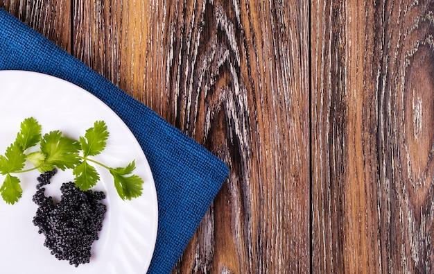 Caviar noir sur une plaque blanche avec des herbes sur la table.