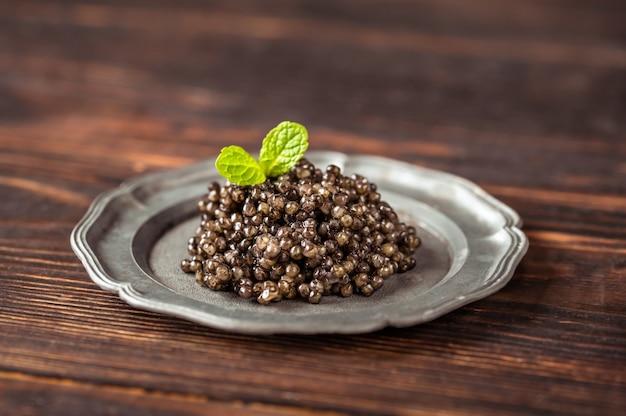 Caviar noir sur plaque vintage argent gros plan