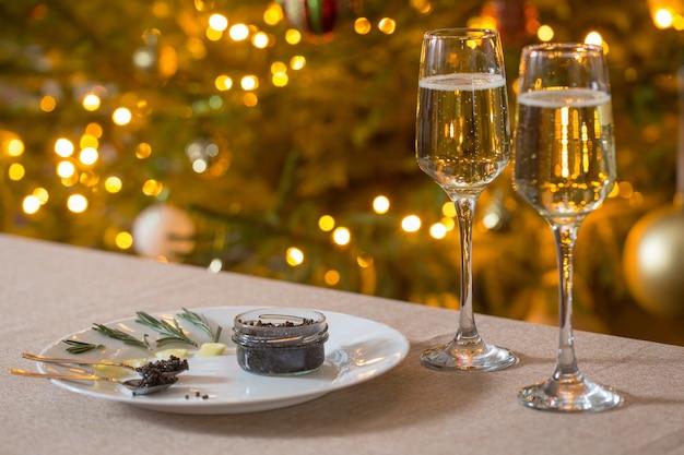 Caviar noir et verre de champagne sur l'arbre de noël