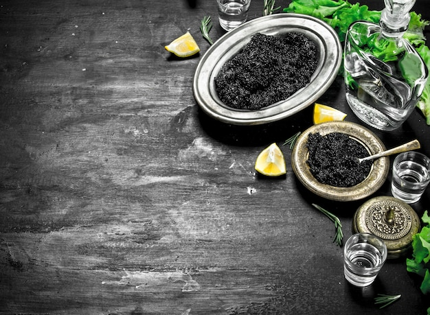 Caviar noir avec vodka et tranches de citron. sur un tableau noir.