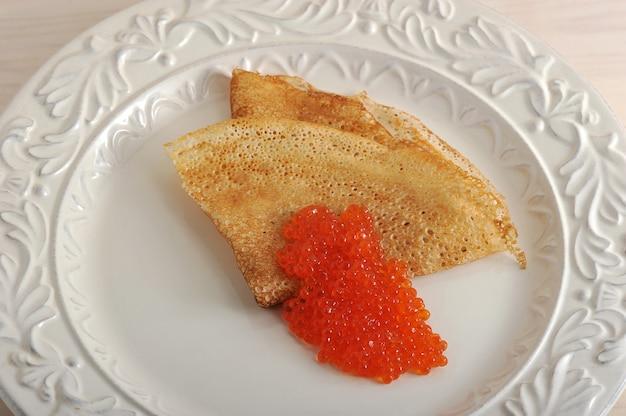 Caviar rouge et crêpes en plaque sur fond en bois