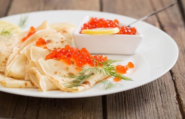 Caviar rouge avec crêpes sur table en bois
