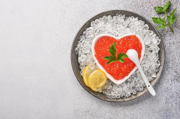 Caviar rouge dans un bol en forme de coeur servi avec du citron et des glaçons sur fond gris table.