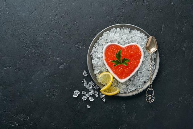 Caviar rouge dans un bol en forme de coeur servi avec du citron et des glaçons sur fond noir table