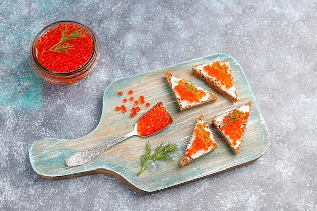 Caviar rouge dans un bol en verre et dans une cuillère, vue de dessus