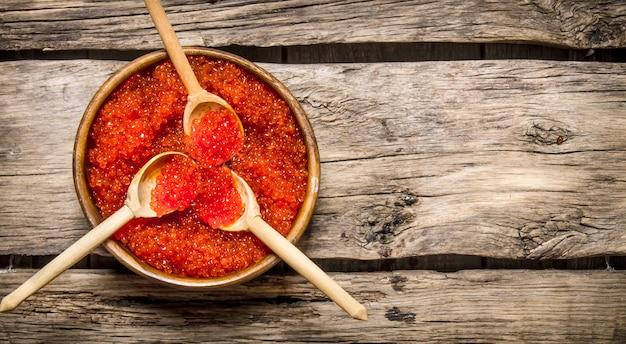 Caviar rouge dans des tasses en bois avec des cuillères. sur une table en bois. espace libre pour le texte. vue de dessus