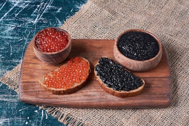 Caviar rouge et noir sur planche de bois.