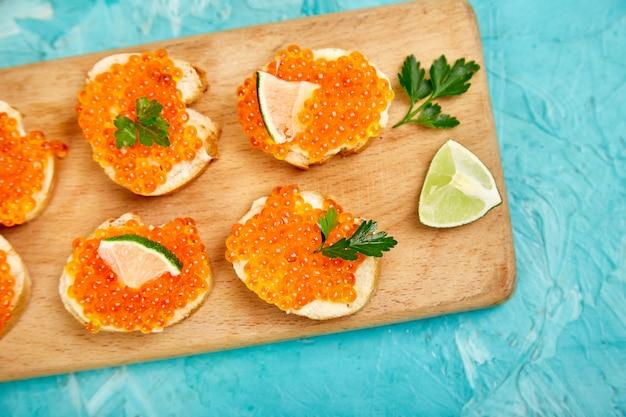 Caviar rouge saumon dans un bol et des sandwiches avec sur une planche à découper en bois