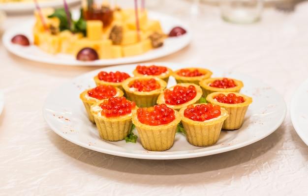 Caviar rouge en tartelettes sur plaque blanche libre