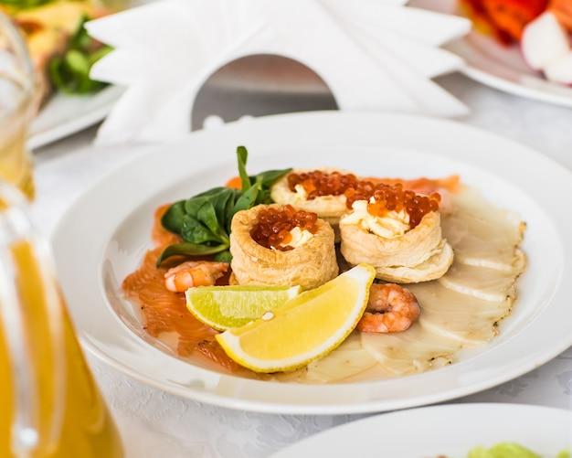 Caviar rouge en tartelettes sur plaque blanche