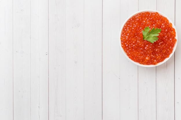 Caviar de saumon rouge dans une assiette sur une table blanche. espace de copie