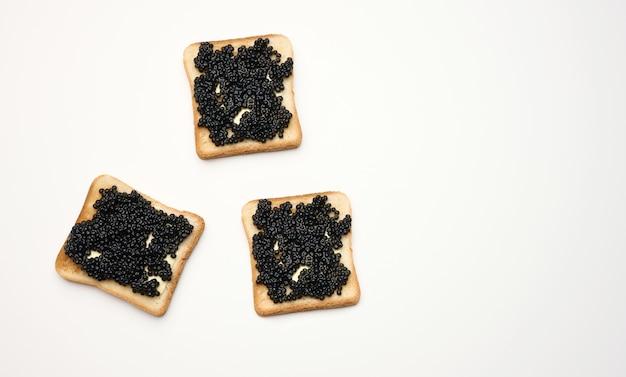 Caviar de spatule sur une tranche carrée de farine de blé blanche. vue de dessus sur tableau blanc, espace de copie