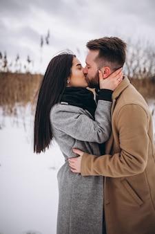 Ccouple s'embrasser dans un parc d'hiver