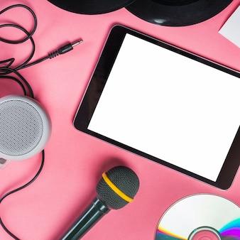 Cd; disque vinyle; microphone; haut-parleur et tablette numérique sur fond rose