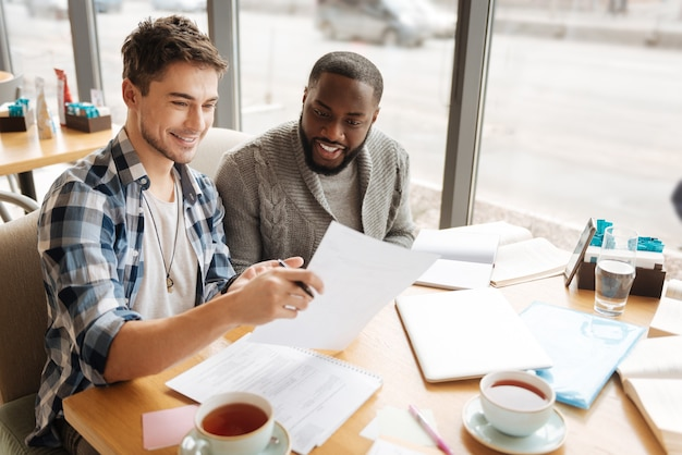 Ceci est la réponse. deux beaux étudiants internationaux lisent des notes ensemble pendant le processus d'étude au café.