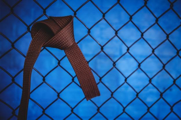 Ceinture marron de karaté suspendu à une clôture en treillis métallique
