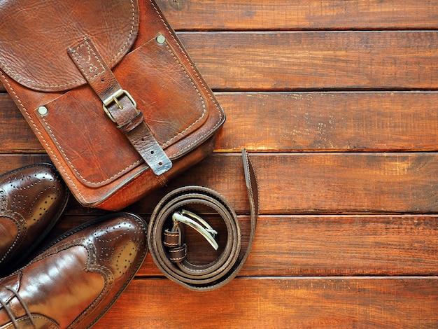 Ceinture porte-documents en cuir et chaussures mans sur fond de bois