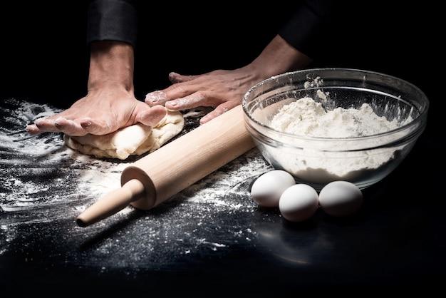 Cela deviendra du pain. gros plan des mains du chef mans pétrir la pâte tout en travaillant dans un restaurant et la cuisine.