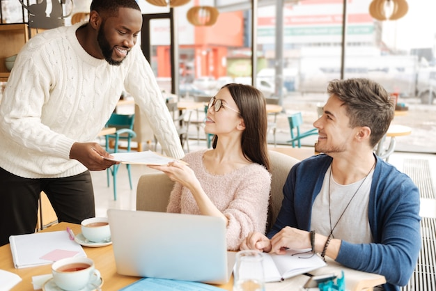 Cela peut aider. heureux jeune homme partage ses notes avec son camarade international tout en étudiant au café.