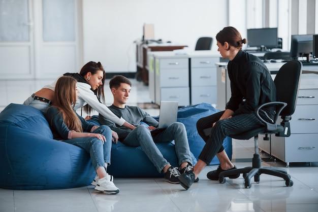 Cela pourrait être une information intéressante. groupe de jeunes en vêtements décontractés travaillant dans le bureau moderne